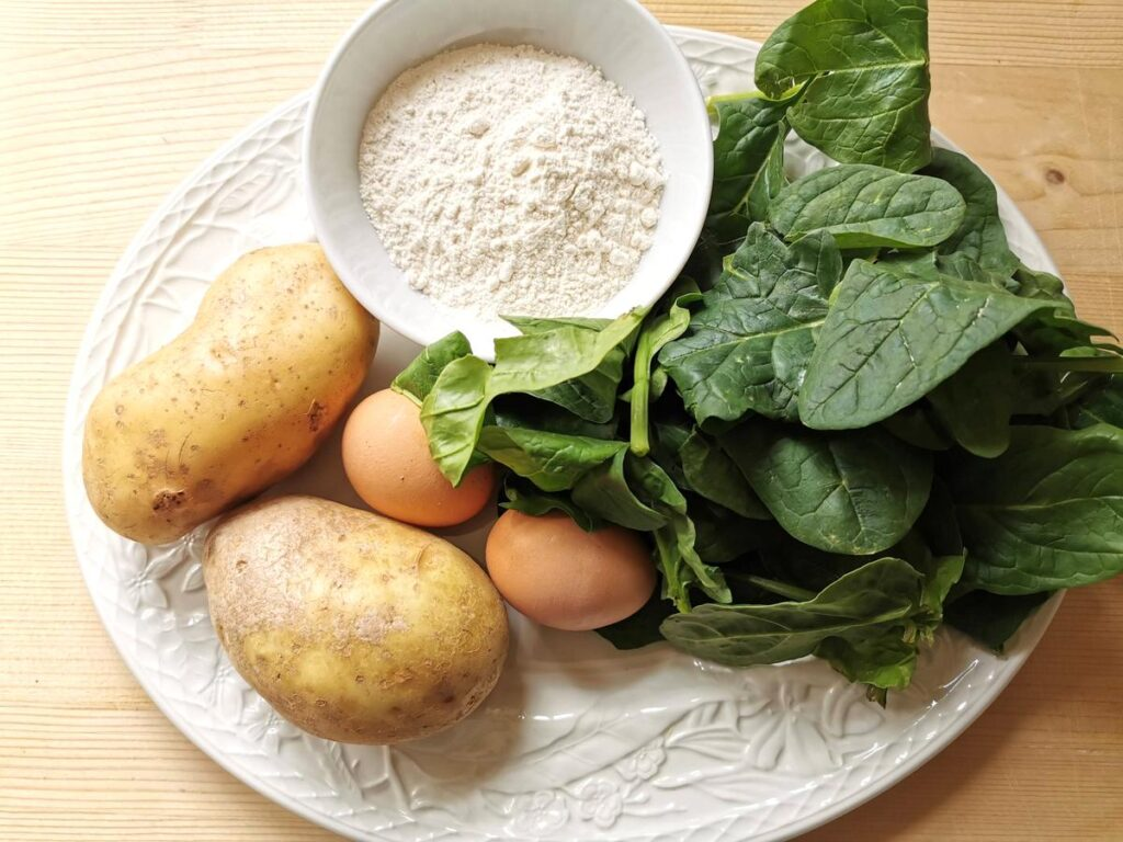 ingredients for spinach and potato gnocchi on white plate.