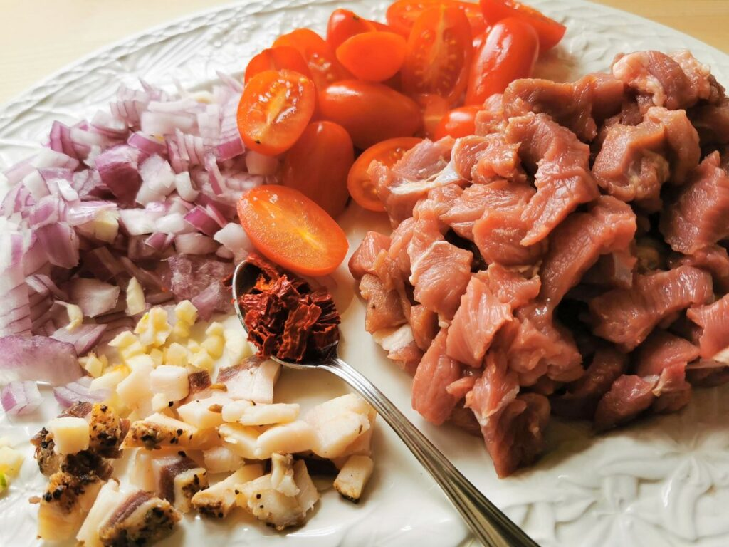 ingredients for lamb ragu prepared for cooking on white plate.