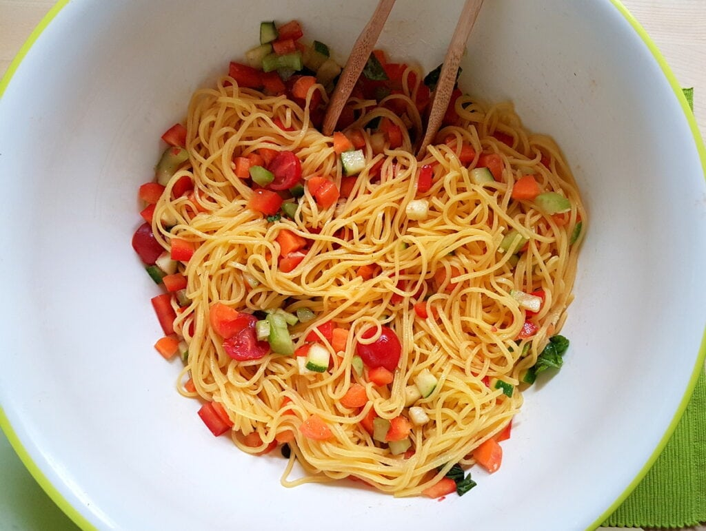 tagliolini and marinated vegetables mixed together in bowl