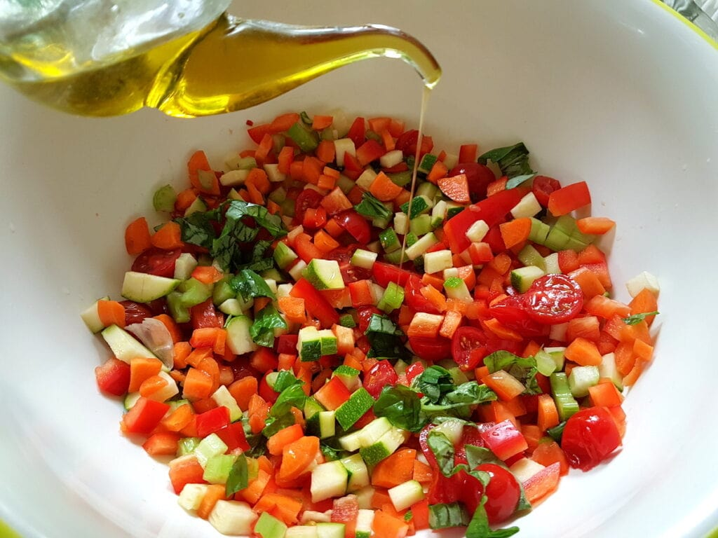 chopped vegetables in bowl with olive oil and lemon juice.