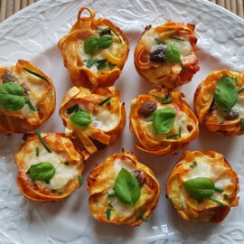 tagliatelle pasta muffin nests on a white oval dish