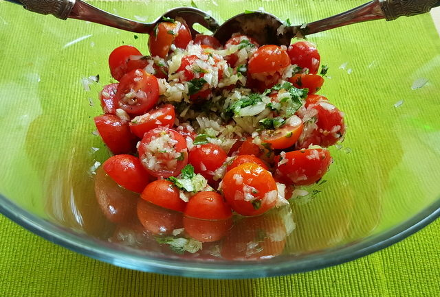 cherry tomatoes, onions and herbs marinating in glass bowl
